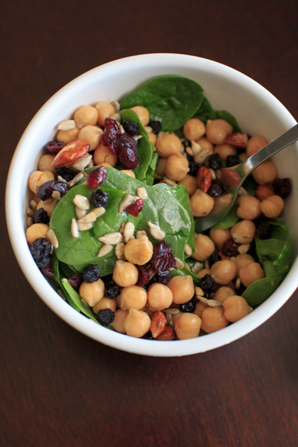 Spinach Chickpea Salad - a bowl of deliciousness! Protein, veggies, fruit, seeds, and nuts = flavor that will make you say goodbye to your normal boring salad.