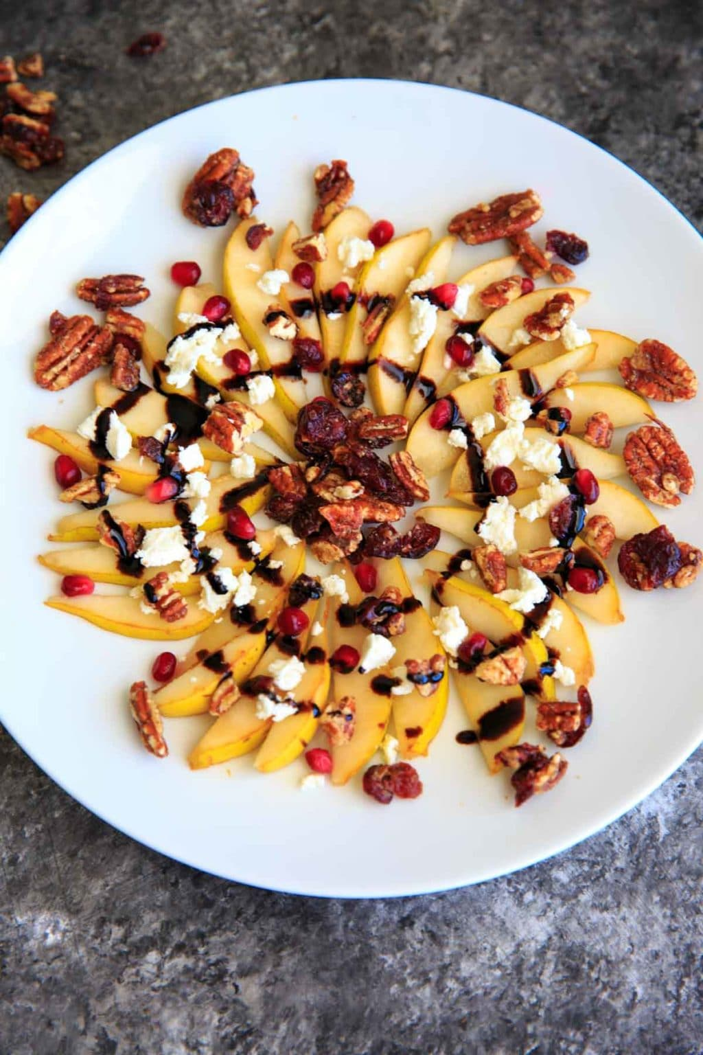Sweet and savory pear nachos with glazes pecans, chevre cheese, pomegranate seeds and balsamic. A unique snack or dessert!