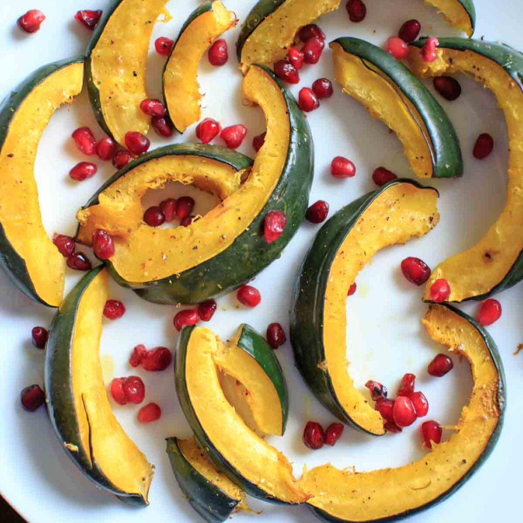 Roasted Acorn Squash with pomegranate seeds. An easy and beautiful side dish for any dinner table.