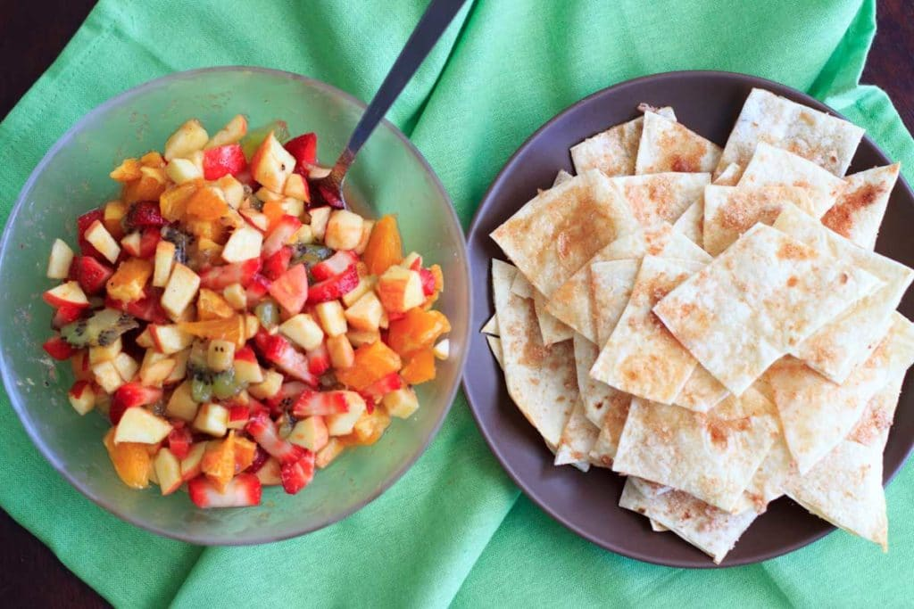 Fruit salsa made from apples, oranges, kiwis and strawberries and tortilla chips baked with cinnamon sugar. Colorful party appetizer or dessert!
