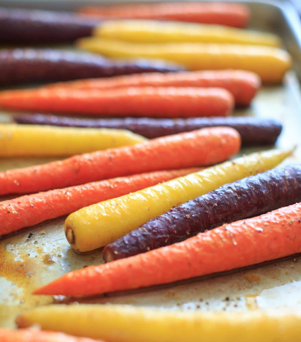 Maple roasted carrots are an easy vegetable side dish that you can throw together for any meal. Vegan and gluten-free, 5 ingredients or less. (Picture is after roasting, angle shot.)