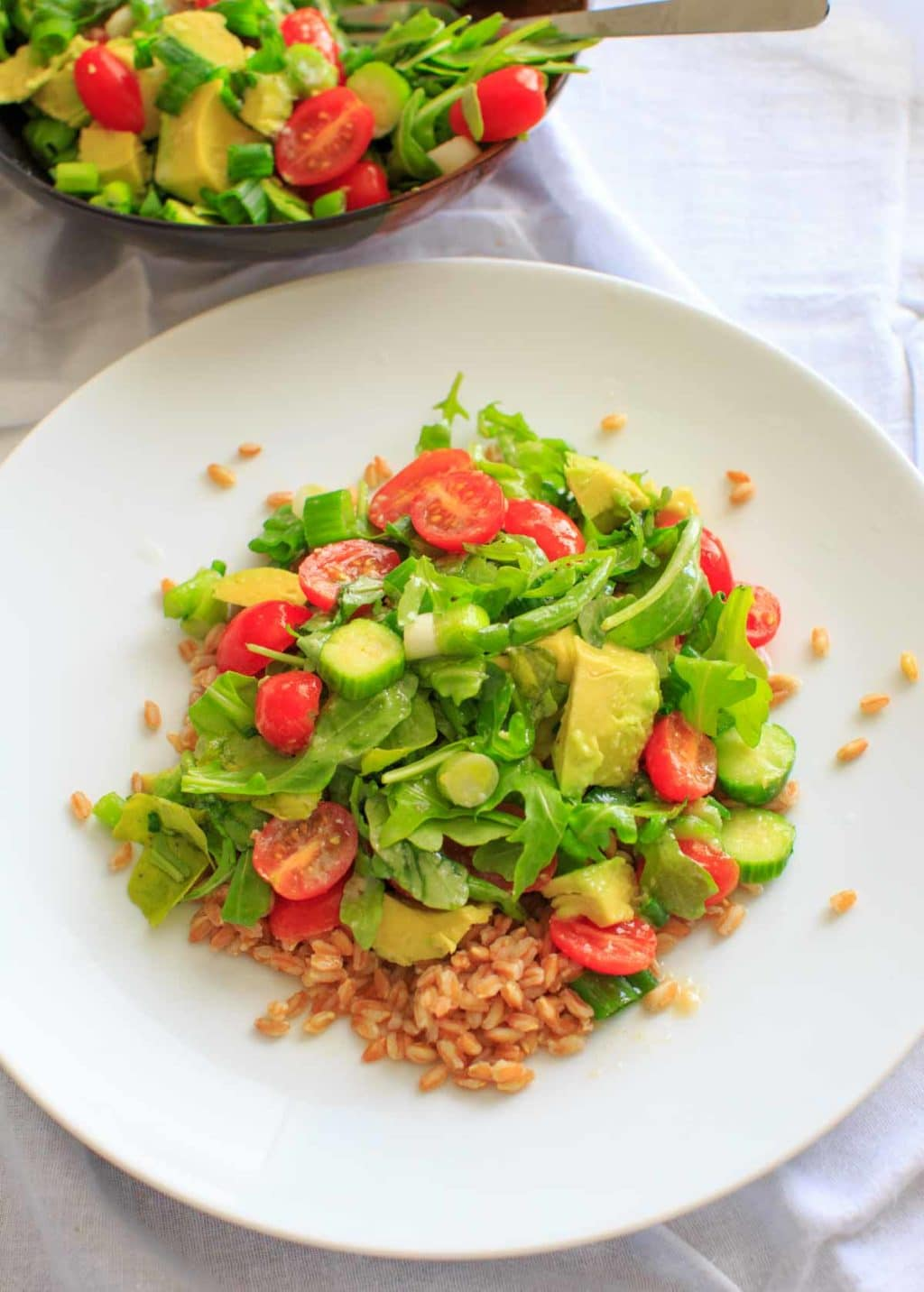 This cucumber avocado salad with miso vinaigrette is full of greens and veggies that can be eaten by itself (for gluten-free) or over a bed of farro for a heartier meal. Either way is a delicious vegan dish that is healthy and full of flavor!