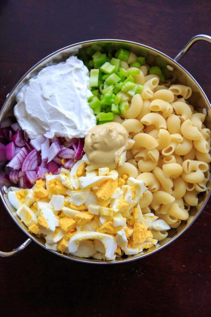 Deconstructed egg salad macaroni with yogurt, pasta, eggs, celery, onion and mustard.