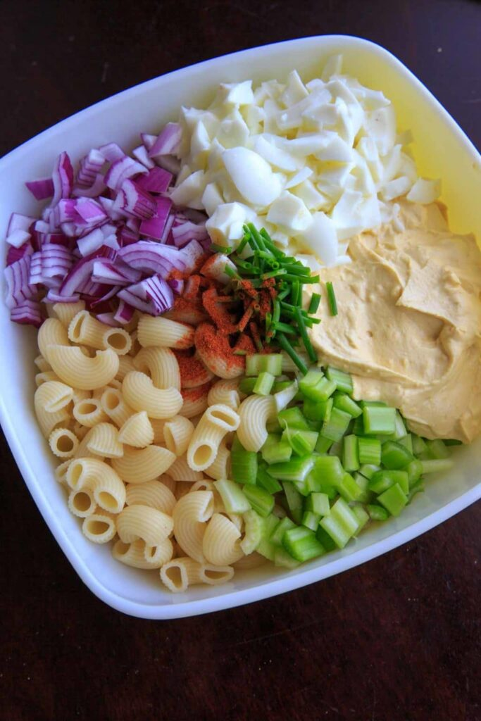 Deconstructed deviled egg pasta salad with macaroni, celery, onion, egg white and deviled egg mixture..