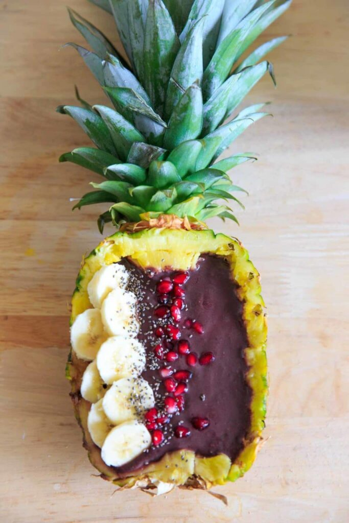 Pineapple Acai Smoothie Bowl or Boat. Full Pineapple with banana, pomegranate arils, and chia seeds.