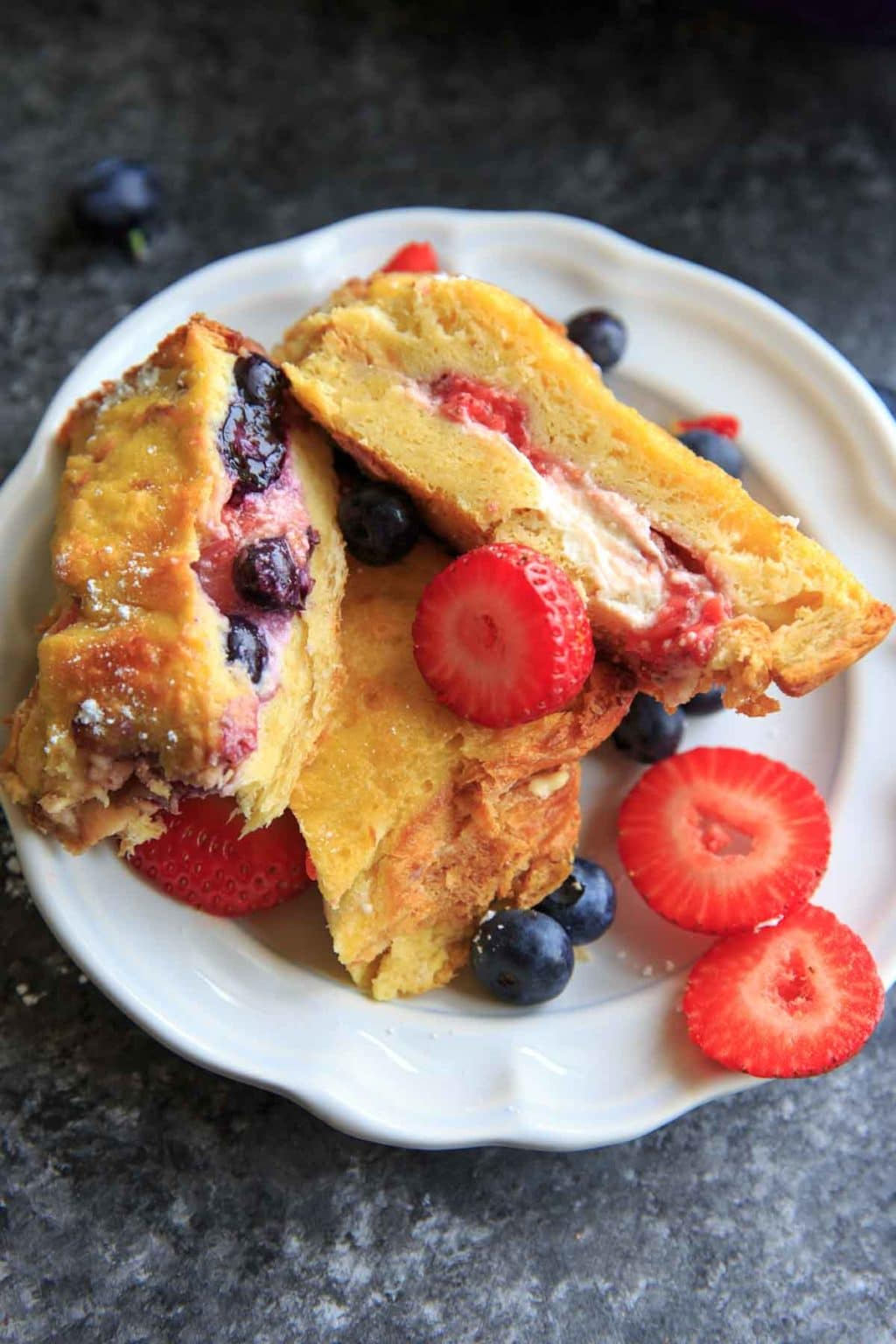 Summer Berry Stuffed French Toast Casserole Bake. Stuffed with cream cheese, fruit jam, strawberries and blueberries and topped with more berries! Serve with a sprinkle of powdered sugar and/or maple syrup if desired. Picture shows stuffed slices cut in half.