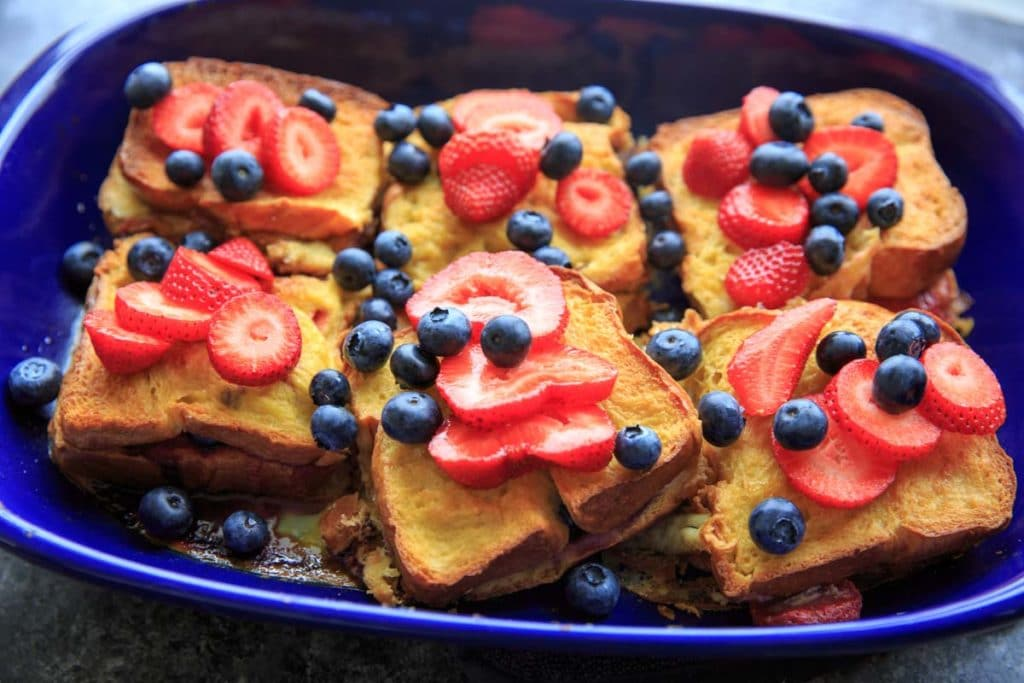 Summer Berry Stuffed French Toast Casserole Bake. Stuffed with cream cheese, fruit jam, strawberries and blueberries and topped with more berries!