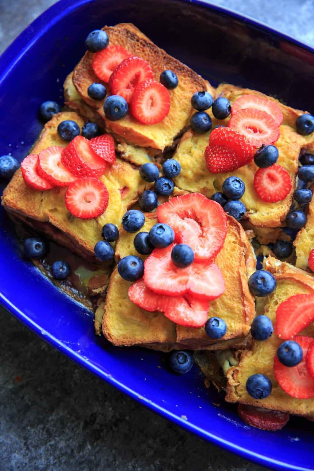 Summer Berry Stuffed French Toast Casserole Bake. Stuffed with cream cheese, fruit jam, strawberries and blueberries and topped with more berries! Serve with a sprinkle of powdered sugar and/or maple syrup if desired. Breakfast or brunch is served!
