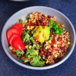 A customizable vegan and gluten-free buddha bowl with kale, quinoa, tomato, avocado, black beans, corn, and more!