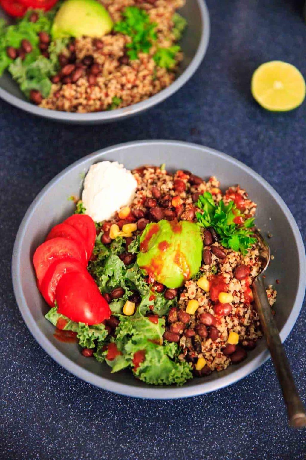 A customizable vegan and gluten-free buddha bowl with kale, quinoa, tomato, avocado, black beans, corn, and more!