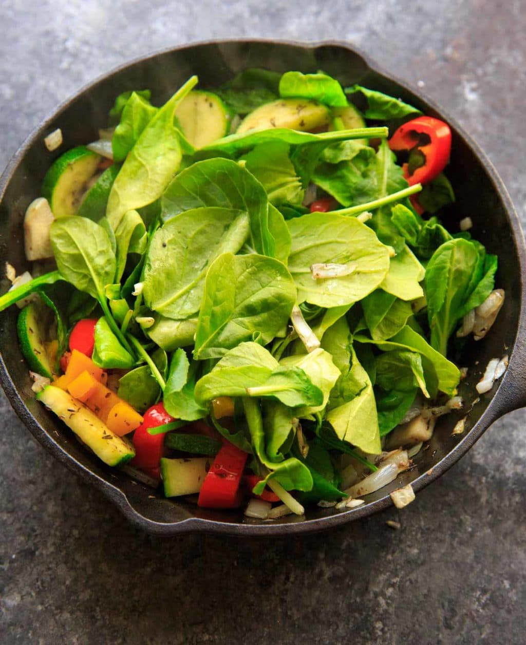 Adding spinach to sauteed vegetables with zucchini, onion, mini sweet peppers
