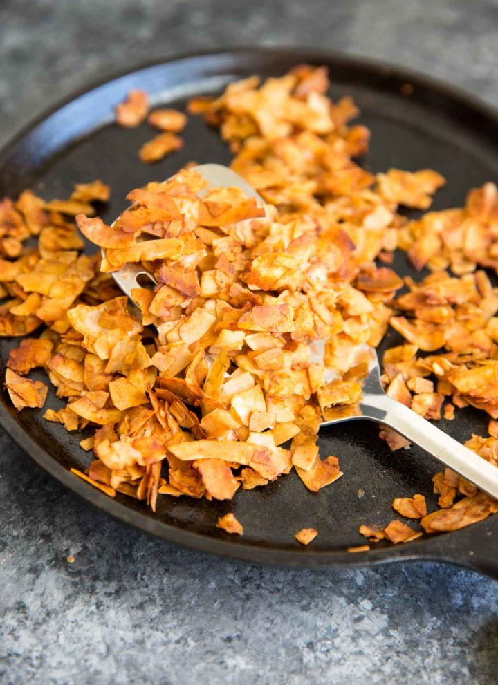 "Coconut Flake ""Bacon"" - Coconut chips/flakes baked with soy sauce or tamari, maple syrup, liquid smoke and a touch of sriracha. Vegan bacon!"