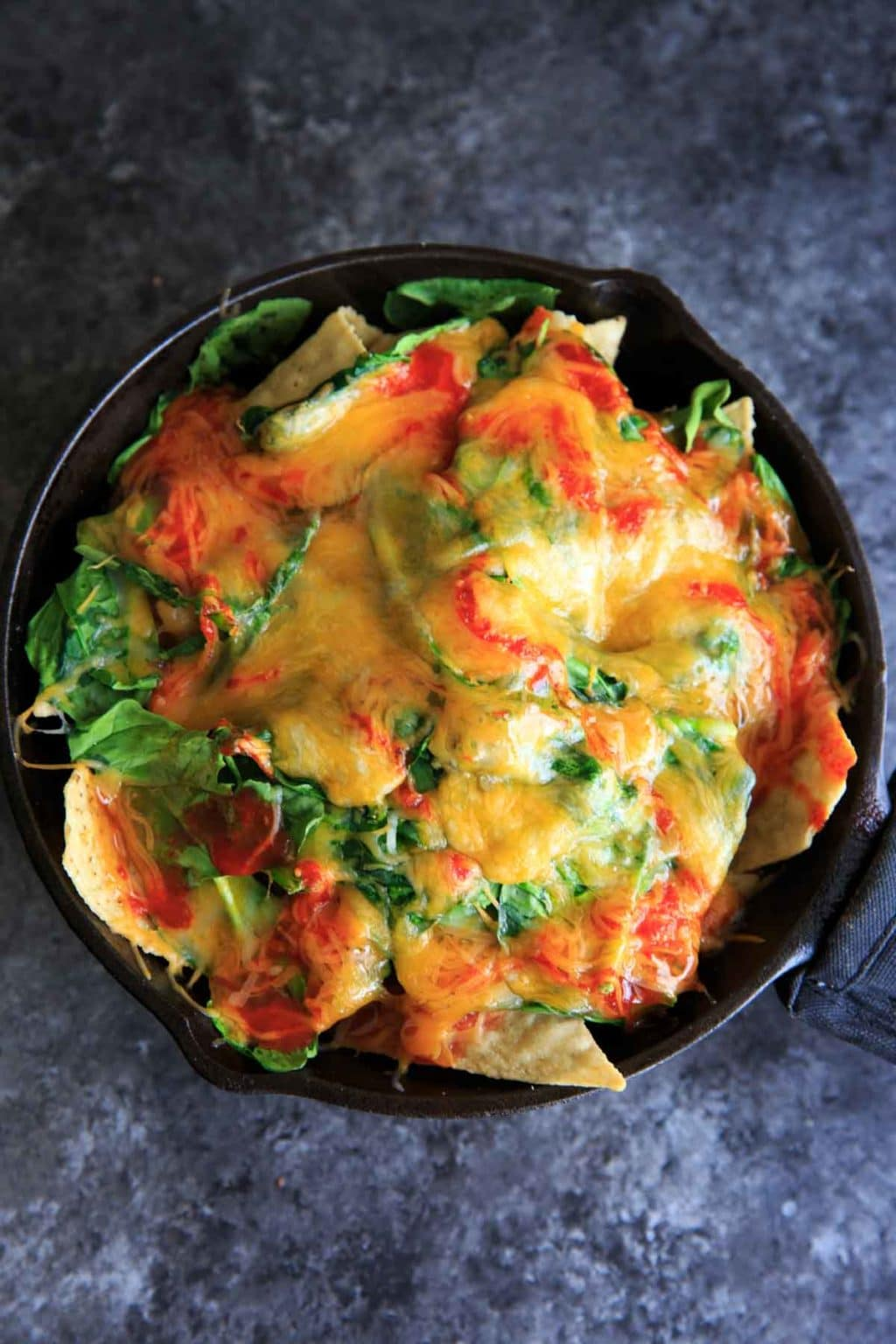 Oven-baked spinach nachos in a cast iron skillet. A great party snack, meal for 2 (or 1!) that has a little extra nutrition with greens.