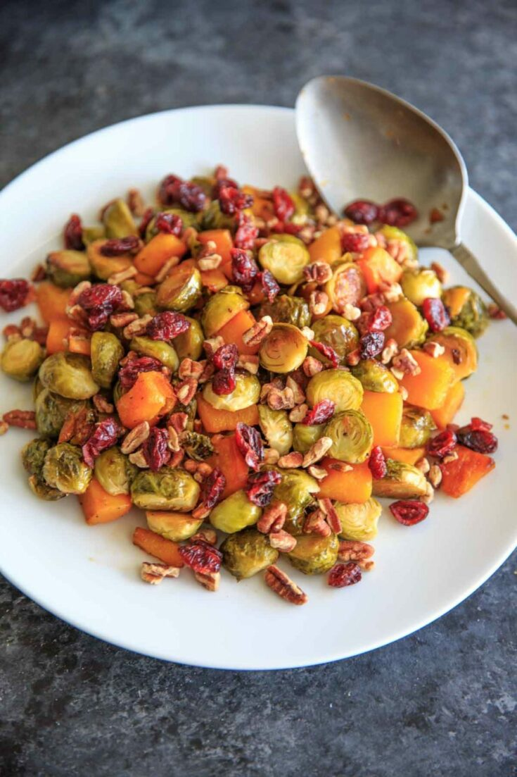 Maple Roasted Brussels Sprout and Butternut Squash with crushed pecans and dried cranberries. A perfect appetizer or side for holiday or fall dinners.