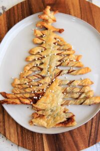 A Christmas-tree shaped dessert made with puff pastry, Nutella and peanut butter. Perfect for sharing at parties, super easy to make and only 3 ingredients. Top with powdered sugar or decorative sprinkles.