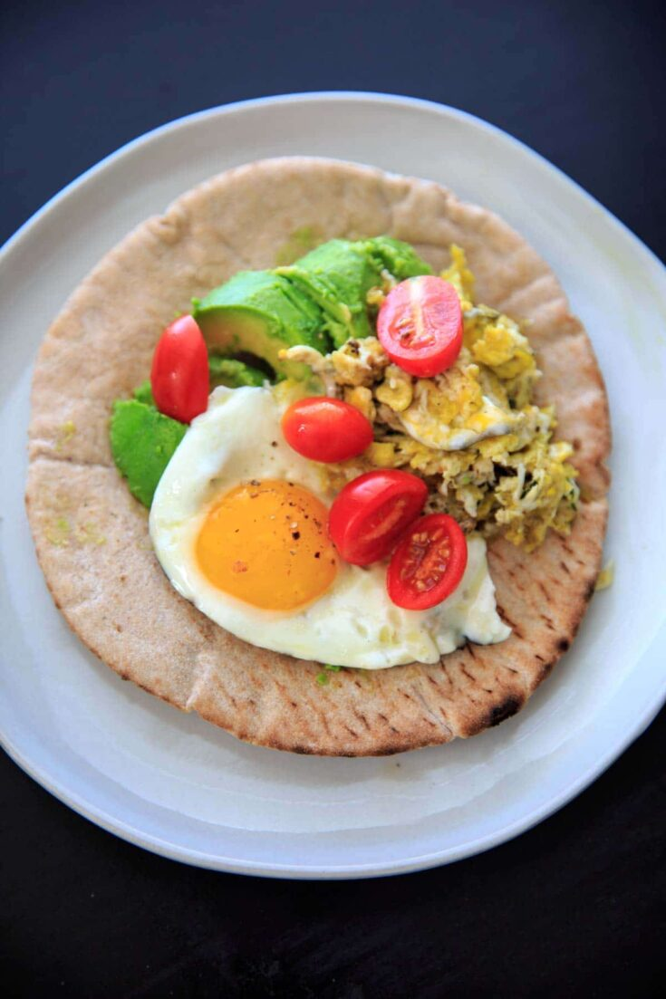 A quick breakfast idea: avocado, tomato, and egg on a pita wrap.