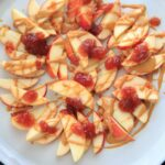 This peanut butter jelly combo on apple nachos is the perfect quick and healthy snack for kids and adults alike! Vegan, gluten-free, protein-packed and delicious.