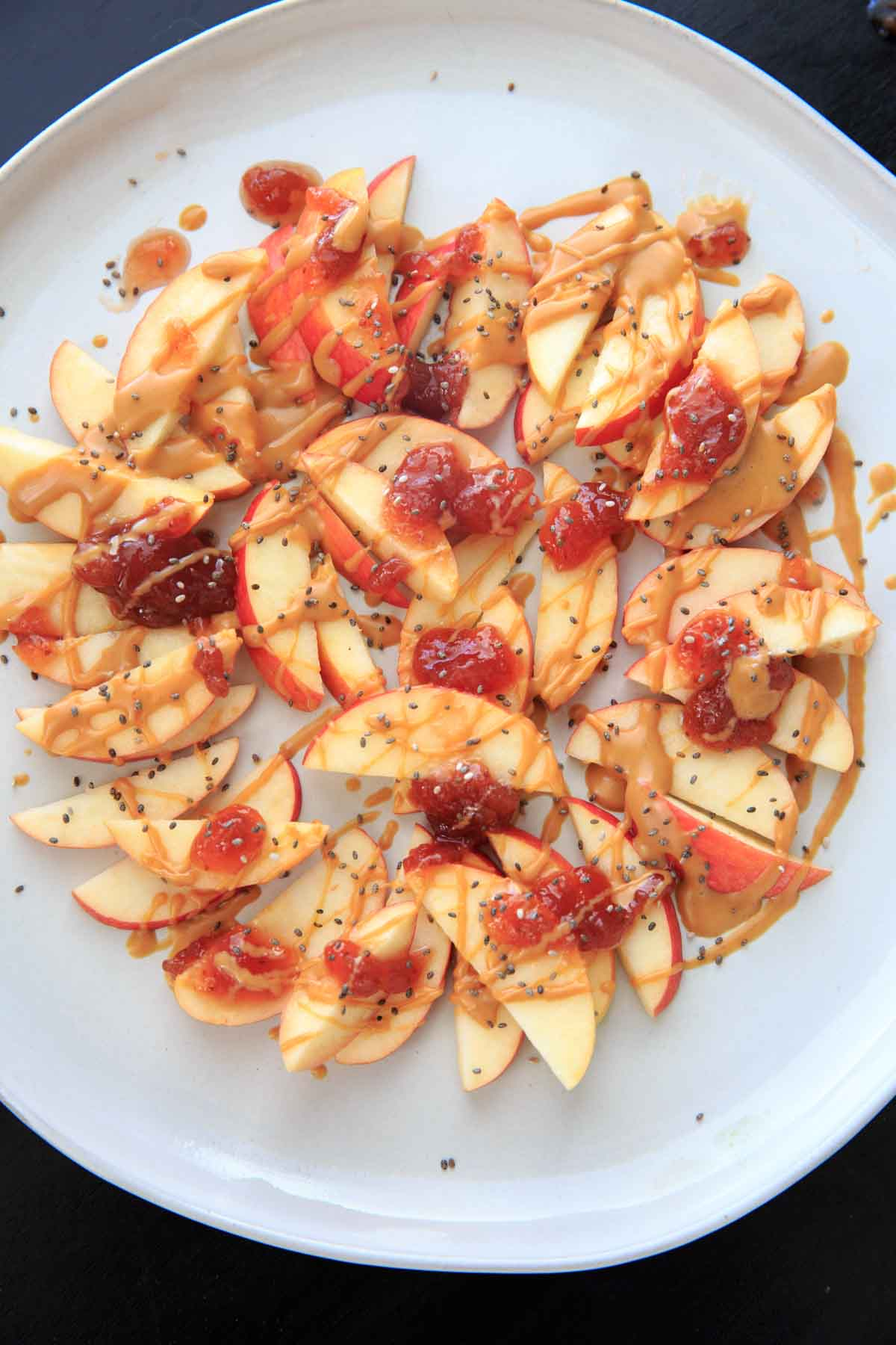 This peanut butter jelly apple nachos recipe is the perfect quick and healthy snack for kids and adults alike! Vegan, gluten-free, protein-packed and delicious.