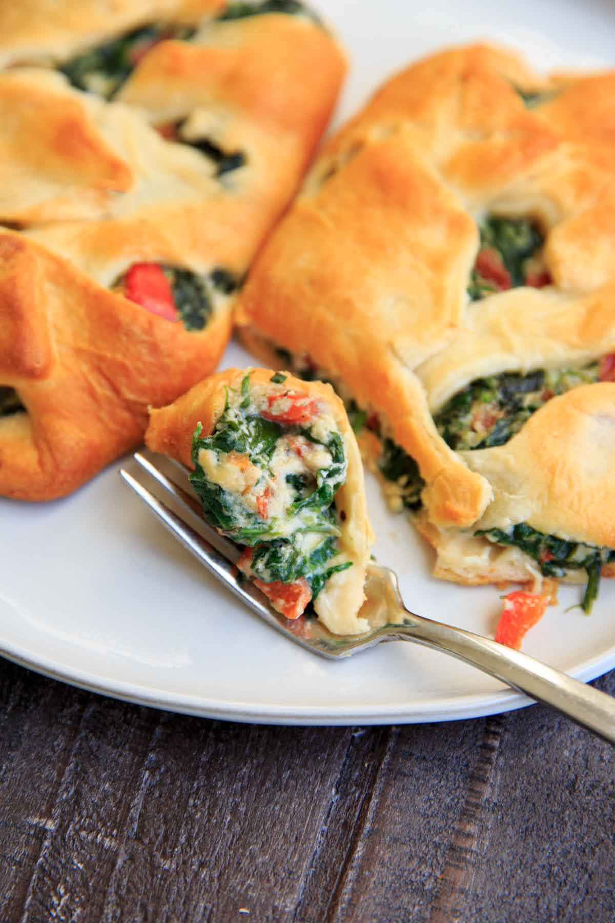 Spinach Ricotta Crescent Wrap cut in half with a bite on fork