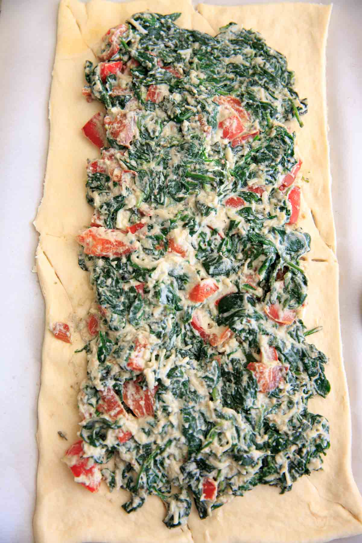 Spinach ricotta mixture spread on crescent wrap before braiding- Spinach Ricotta Crescent Wrap
