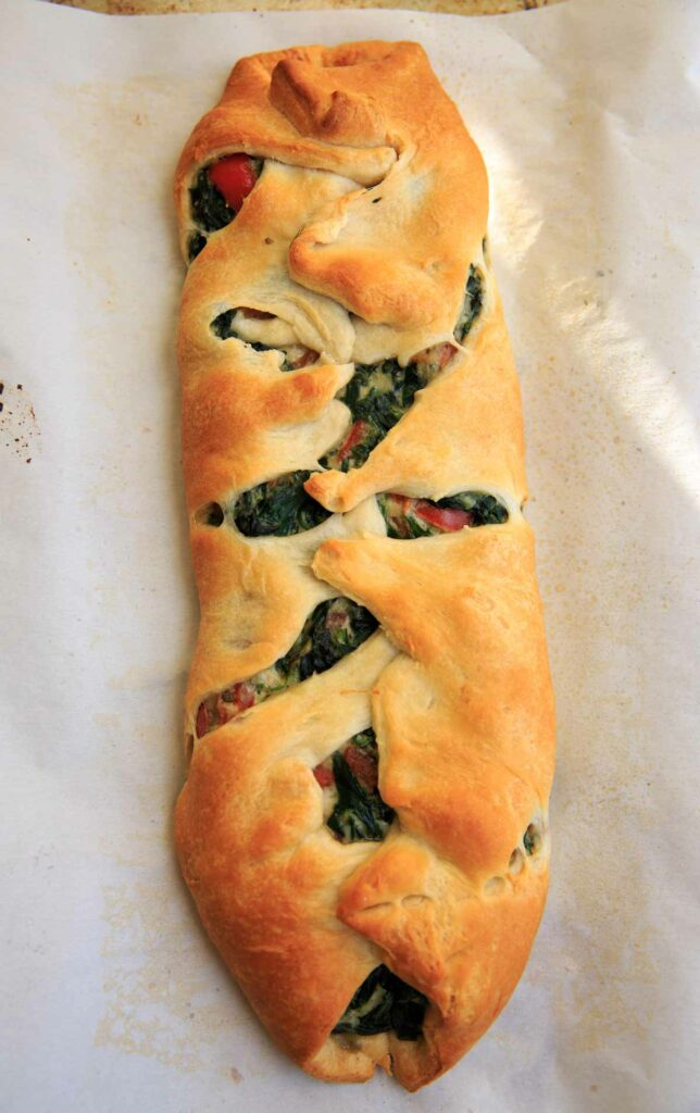 Baked and braided spinach ricotta mixture on crescent wrap - Spinach Ricotta Crescent Wrap