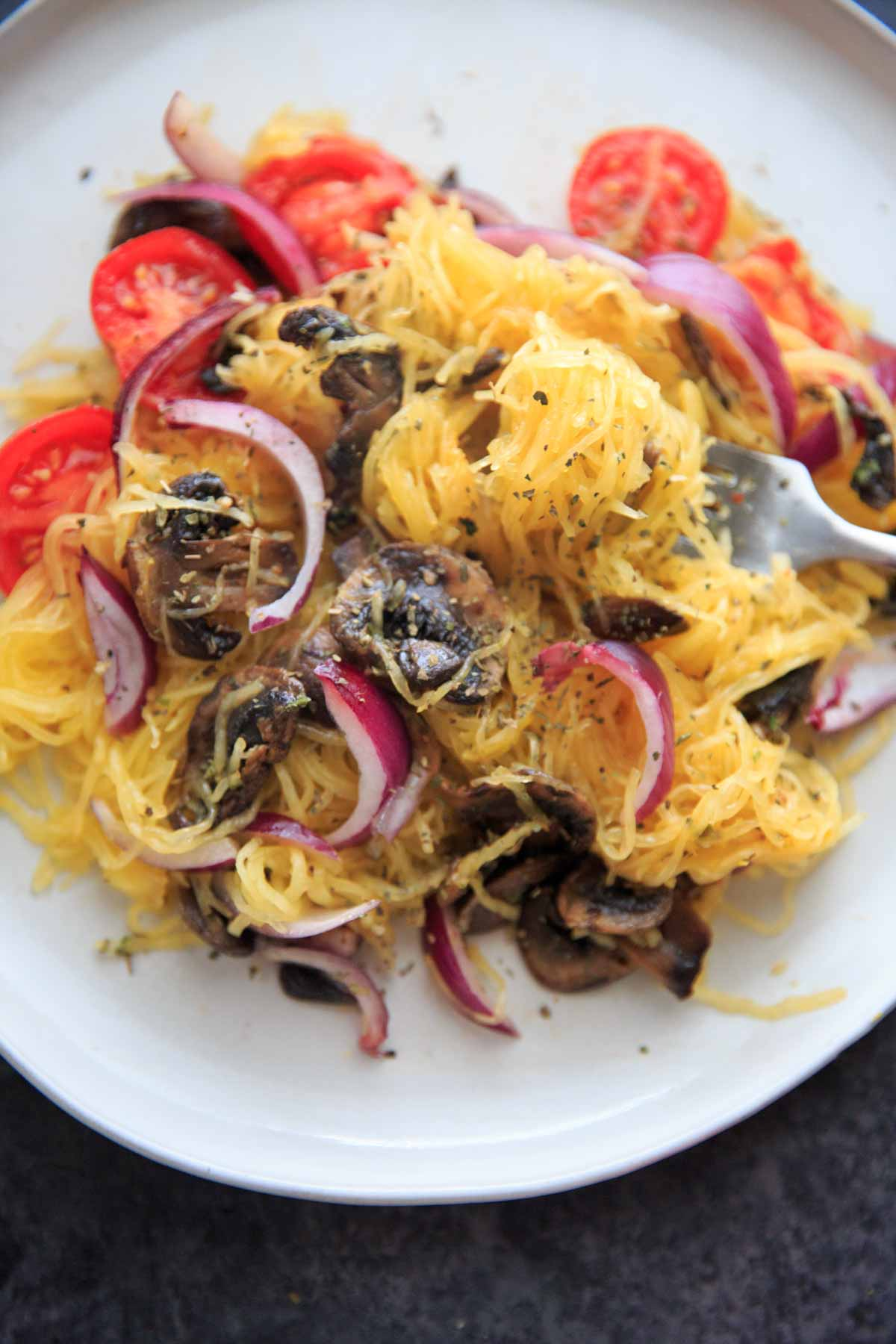 Spaghetti Squash with sauteed mushrooms, tomato and onion. A low-carb, gluten-free and vegan meal full of vegetables and flavor.