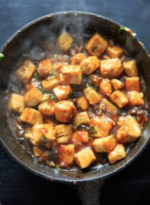 General Tso's Tofu cooking in a cast iron pan. Recipe from Chloe Flavor cookbook