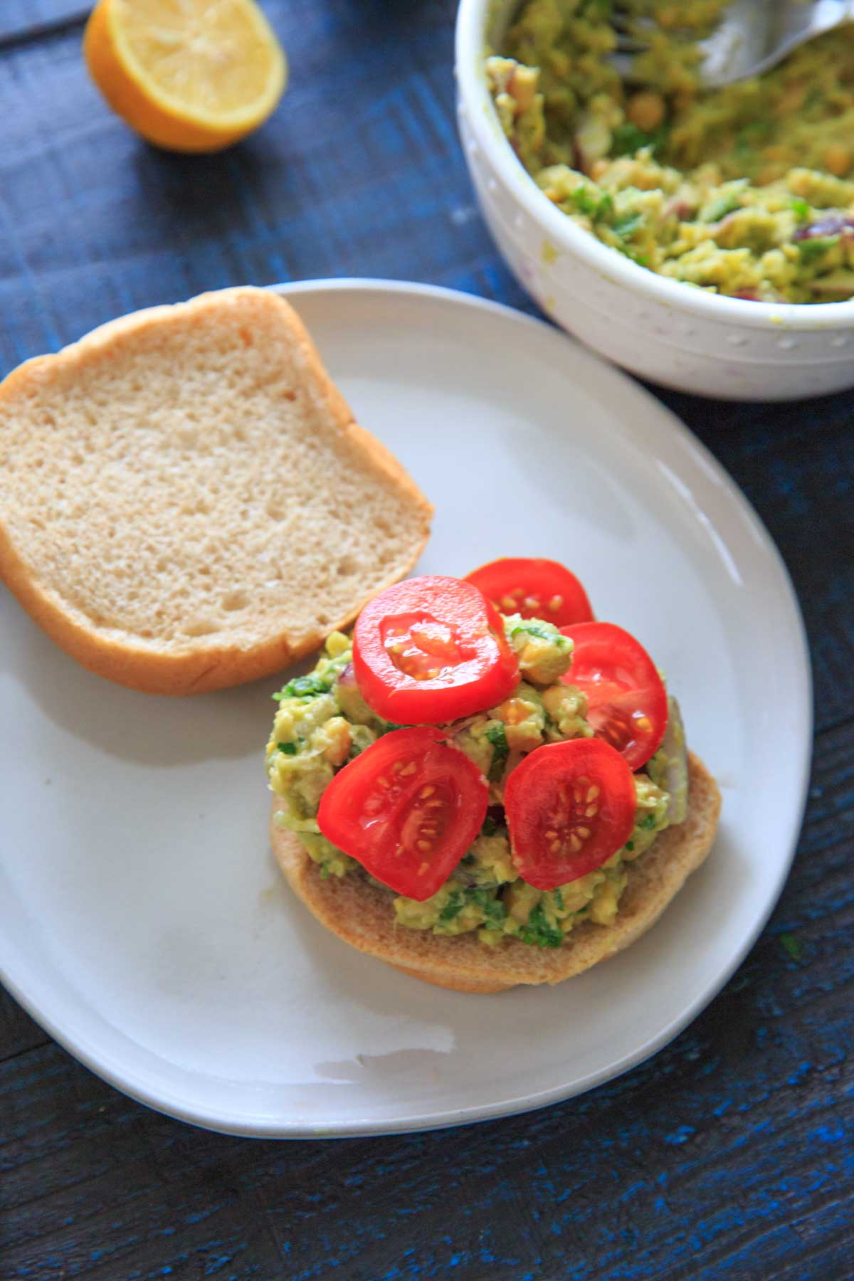 Smashed Avocado and Chickpea Salad on a bun with tomato