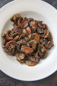 Chili White Button Mushrooms - sliced mushrooms caramelized in garlic and olive oil, topped with chili flakes and parsley. A deliciously easy, spicy and unexpected veggie side dish!