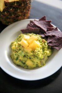 Pineapple Jalapeno Guacamole is a tropical spin on this favorite appetizer dip. Great for summer gatherings, cookouts and gatherings! Serve this vegan and gluten-free snack with corn chips, crackers or veggies.
