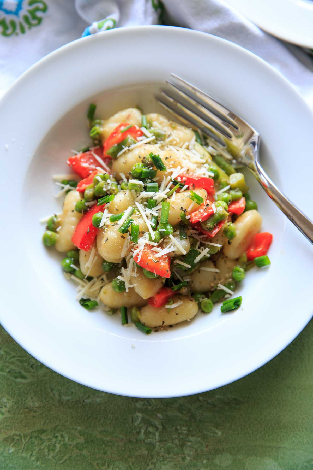 Spring Vegetable Gnocchi with asparagus, peas and herbs. Option to add a touch of parmesan cheese or leave off to keep it vegan! A delicious and fresh tasting pasta dish that's not too heavy and loaded with veggies.