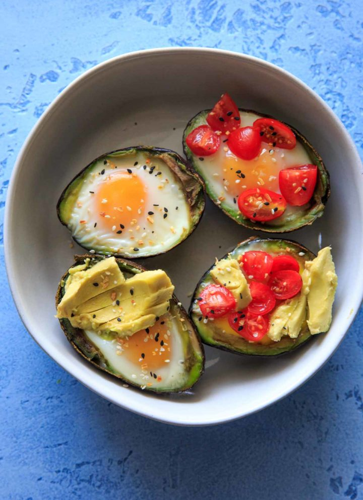 "Baked Egg in Avocado's (Avocado ""Nests"") are a fun way to have a balanced snack or breakfast. Customizable with toppings and will last a day or two in the fridge, so you can bake ahead if needed! Low-carb, protein, fiber and healthy fats."