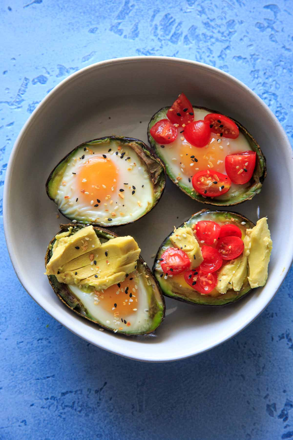 "Baked Egg in Avocado (Avocado ""Nests"") are a fun way to have a balanced snack or breakfast, or a cute mini serving for a brunch! Customizable with toppings and will last a day or two in the fridge, so you can bake ahead if needed! Low-carb, protein, fiber and healthy fats."