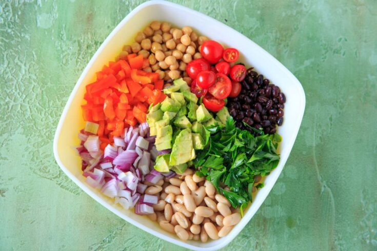 Three Bean Salad with avocado, vegetables and herbs. A flavorful vegan and gluten-free side dish perfect for a picnic or potluck, and filling enough for a main dish!