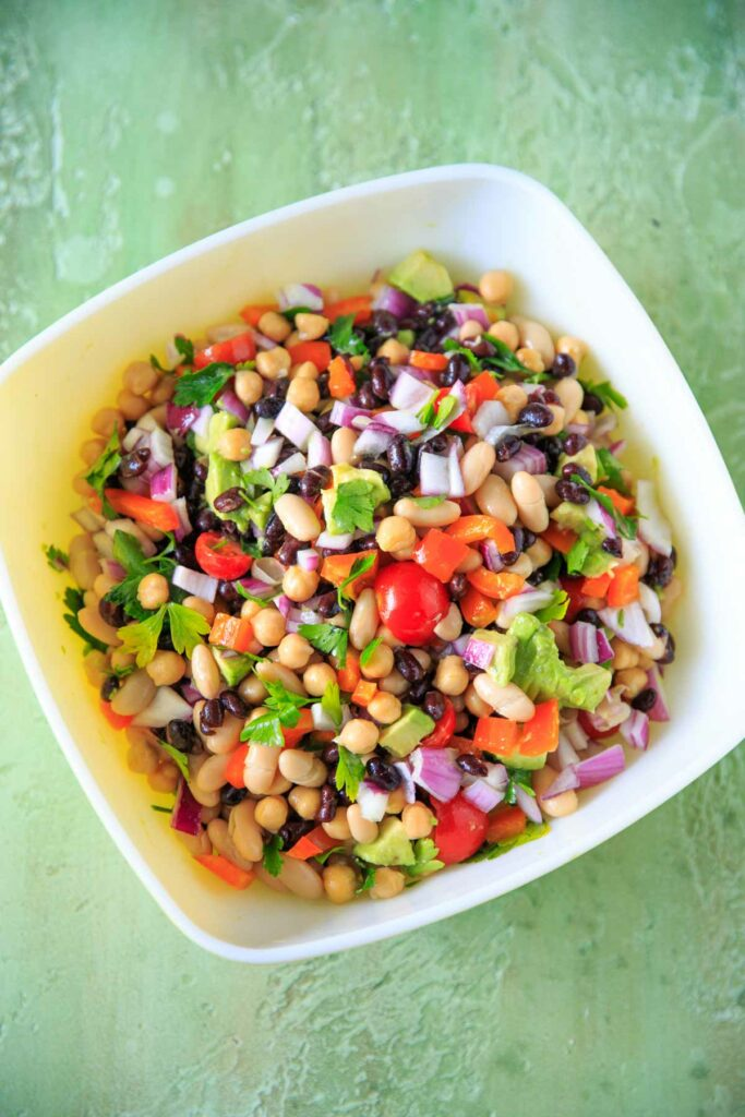 Three Bean Salad with avocado, vegetables and herbs in a large bowl