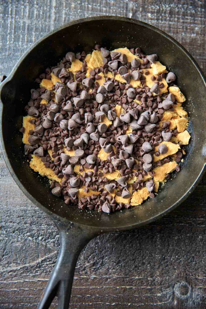 Crumbled graham crackers and chocolate chips ( regular and mini chips) in a cast iron pan