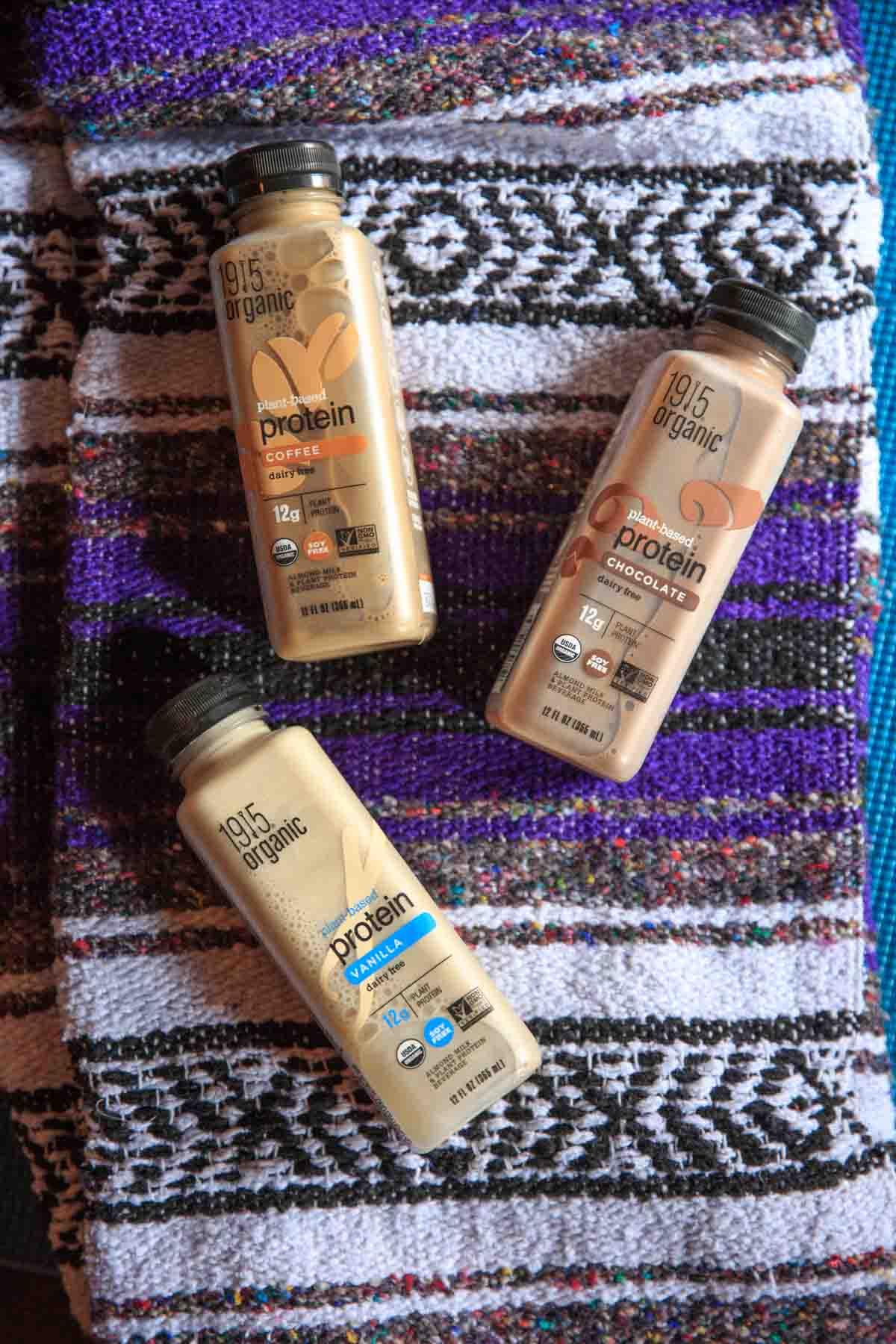 1915 Organic Protein Drink - Chocolate, Vanilla and Coffee on yoga mat and blanket