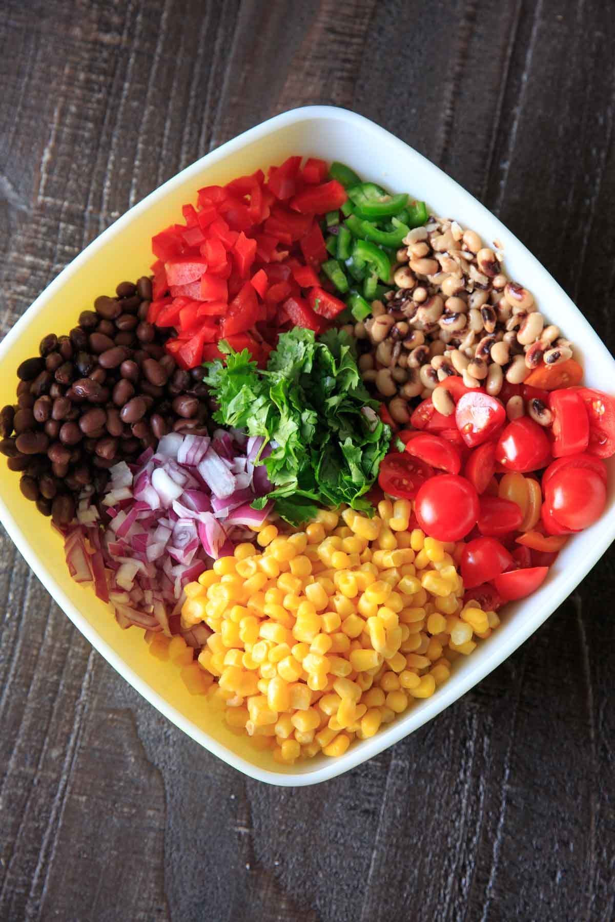 Assembling cowboy caviar with black eyed peas, black beans, onion, tomato, corn, cilantro and bell pepper