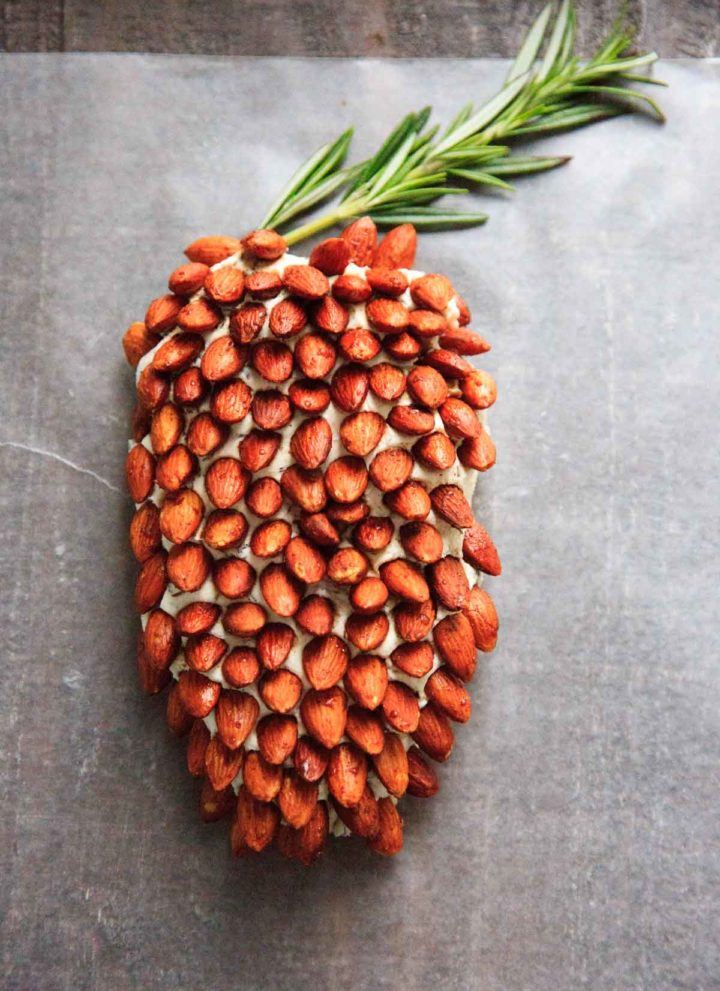 A cheese ball that looks like a pine cone! This will be a hit at your party. Using rosemary sprigs and cinnamon honey roasted almonds.