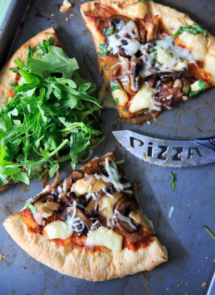 Homemade pizza with caramelized onions, fresh baby arugula and brie cheese!