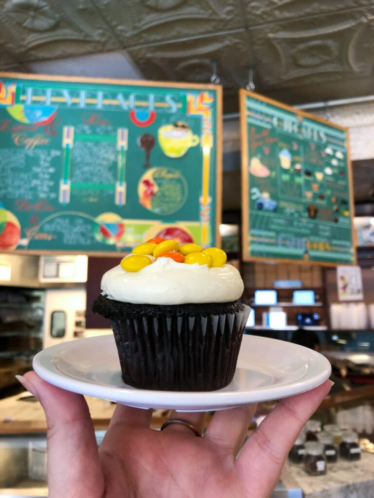 Molly's cupcake - chocolate cream cheese icing and reeses pieces in front of menu