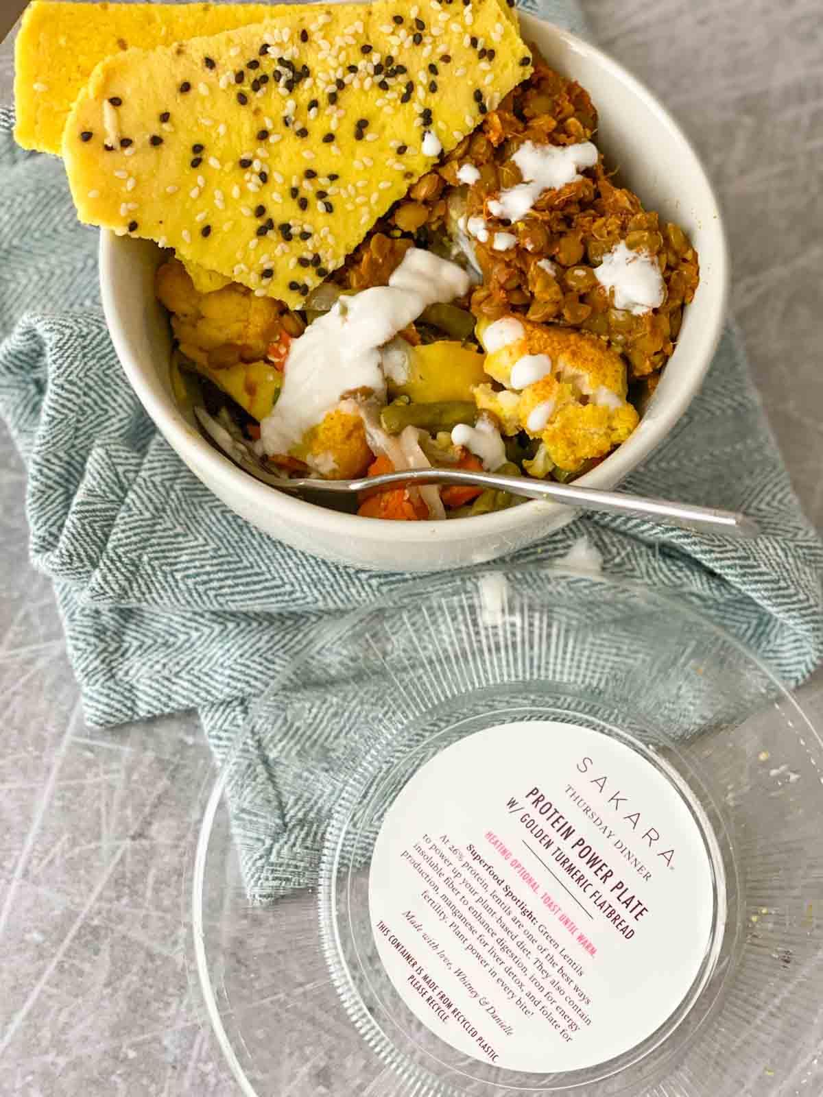 Sakara protein power plat in bowl, turmeric flatbread on side