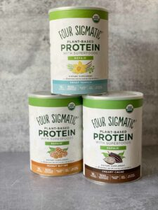 3 canisters of four sigmatic protein powders - peanut butter, sweet vanilla, creamy cacao