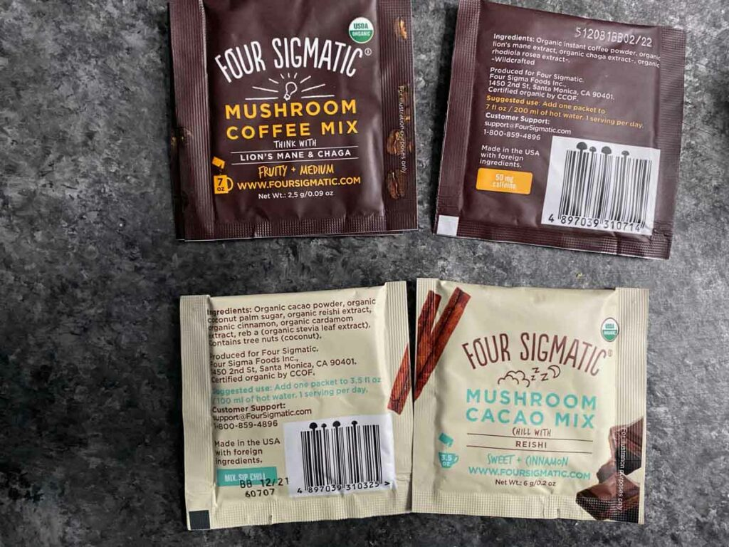 Four Sigmatic coffee and cacao packets with ingredients