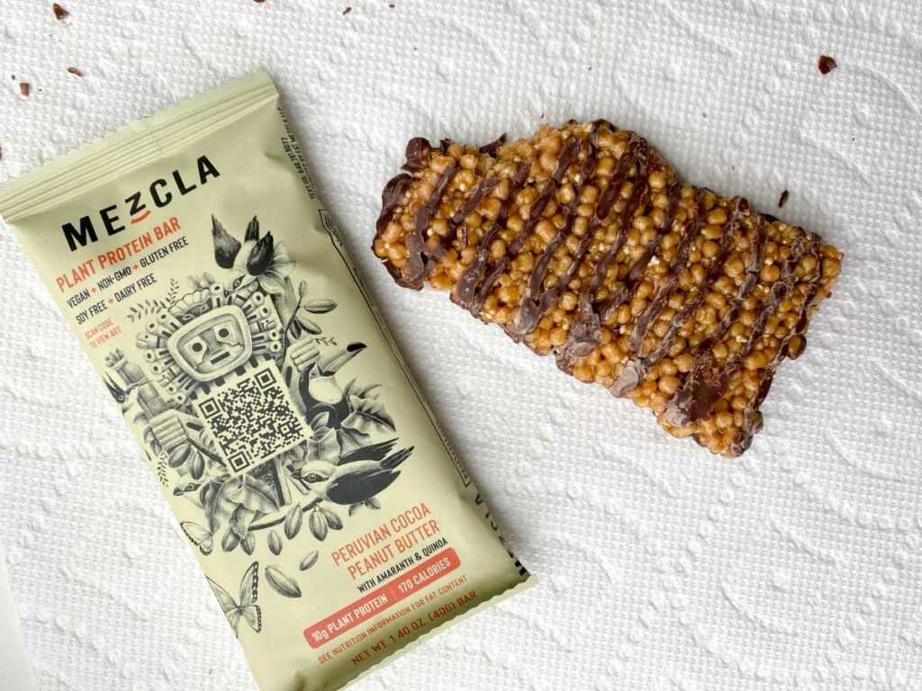 Peruvian Cocoa Peanut Butter flavor of Mezcla plant based bar, bite taken out of it outside of package