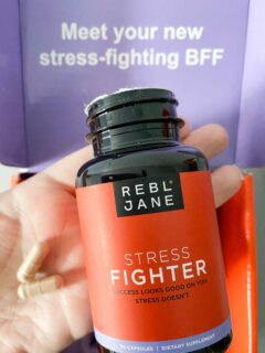 Holding Rebl Jane Stress Fighter bottle and two capsules