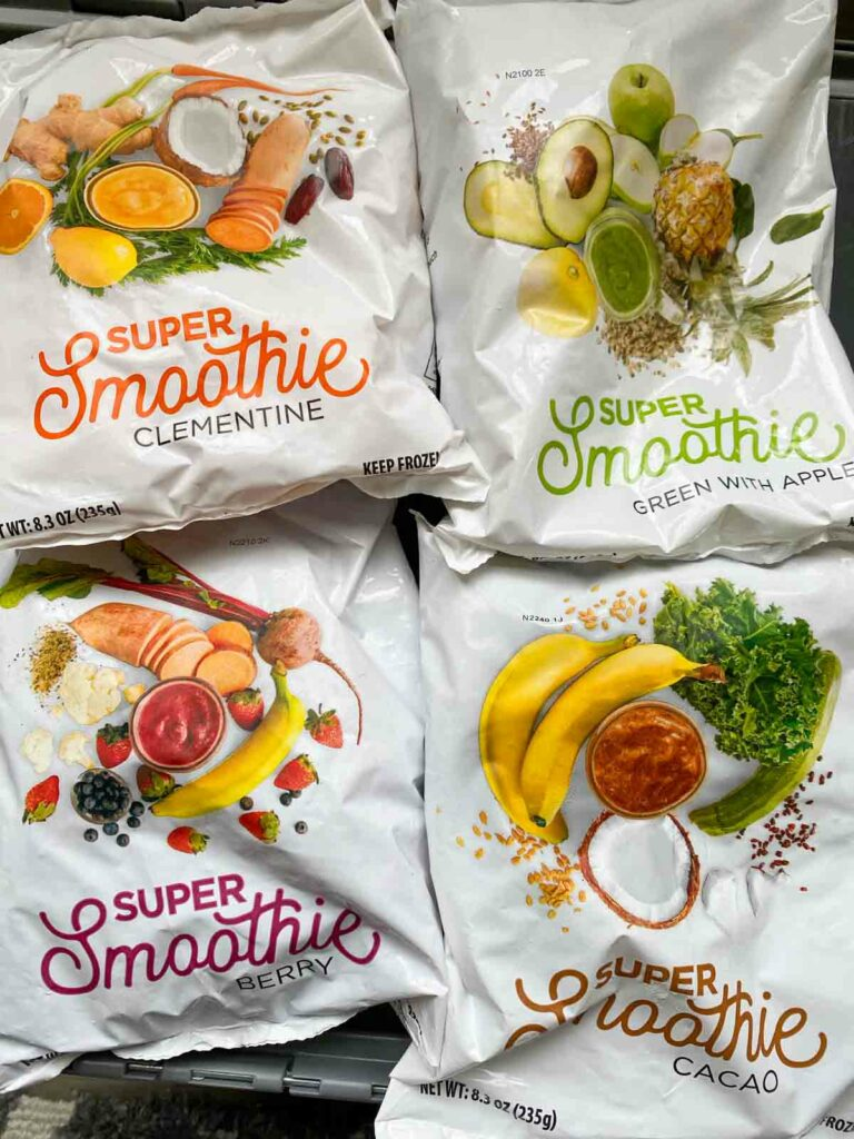four bags of SmoothieBox smoothies, one in each flavor - clementine, apple with greens, berry, cacao