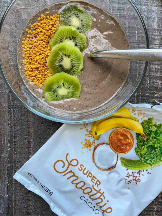 SmoothieBox Cacao flavor super-smoothie in a smoothie bowl, topped with kiwi slices and bee pollen