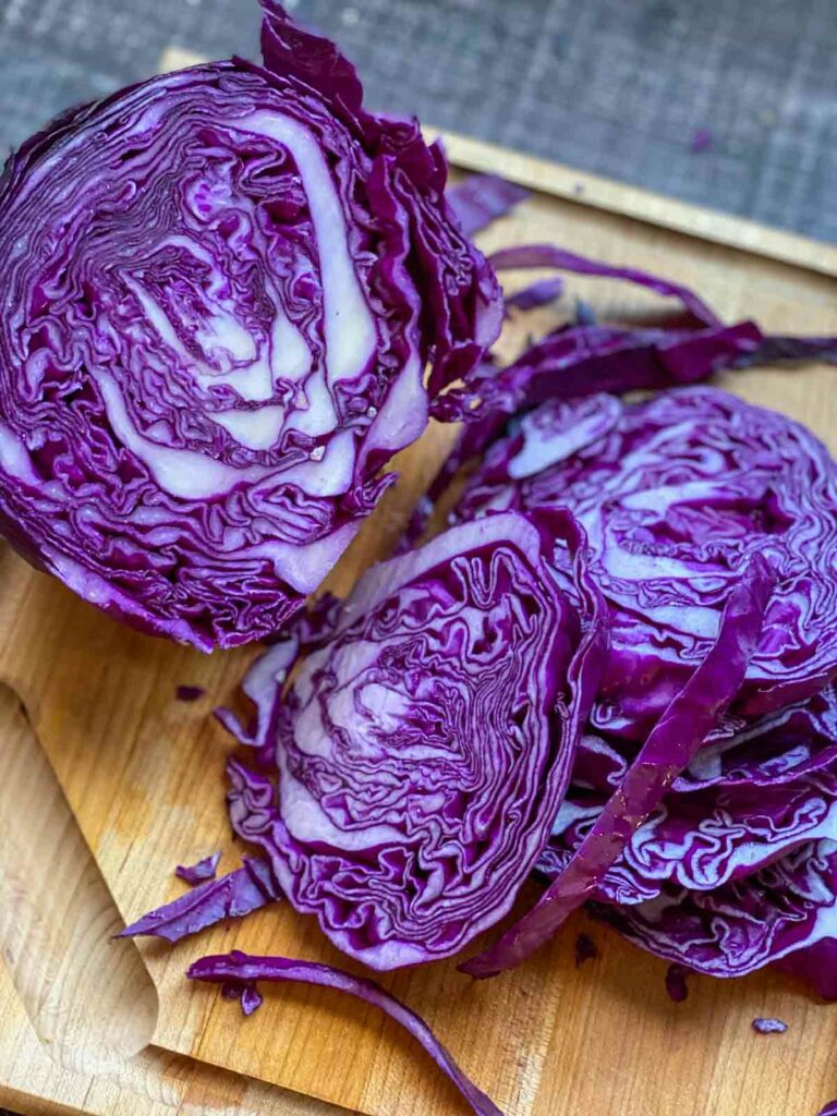 slicing up purple cabbage on cutting board