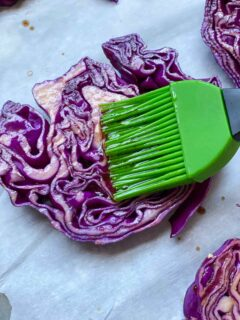 brushing on balsamic vinegar to a slice of red cabbage steaks